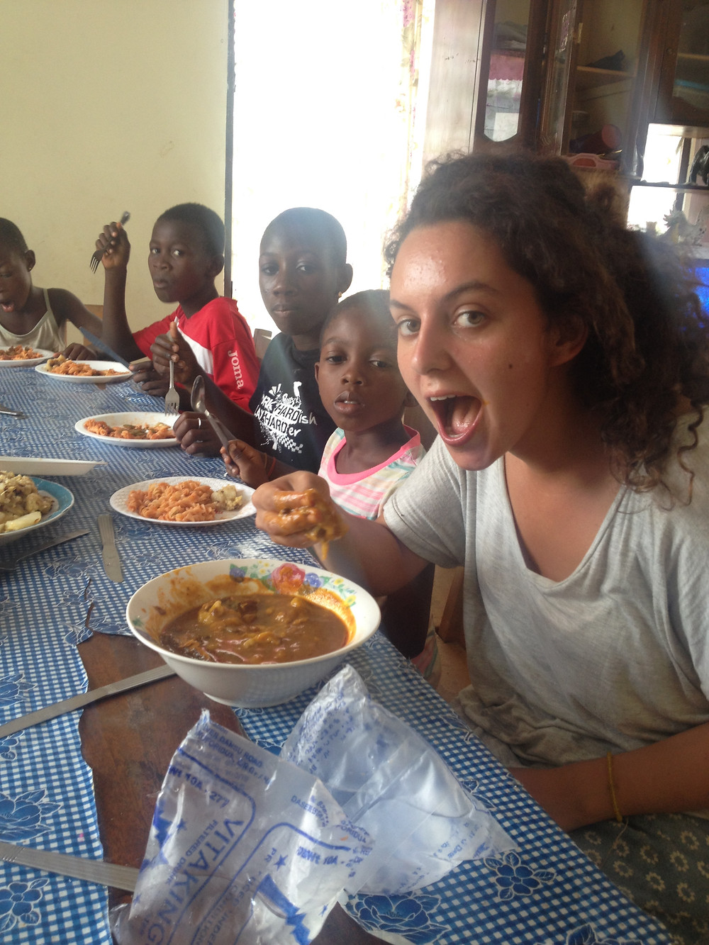 La obruni come banku mientras los niños comen macarrones que desearían cambiar por el banku.