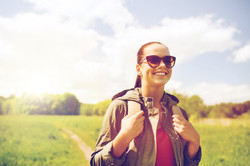 travel, hiking, backpacking, tourism and people concept - happy young woman in sunglasses with backp