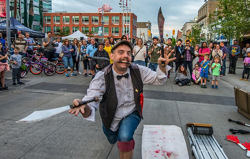 Buskin downtown Kitchener with a crowd of people with juggling machetes