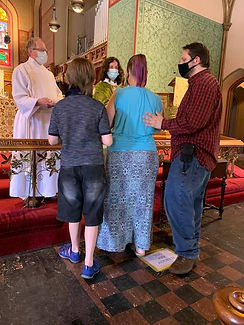 Whitcomb family recieves Holy Communion.