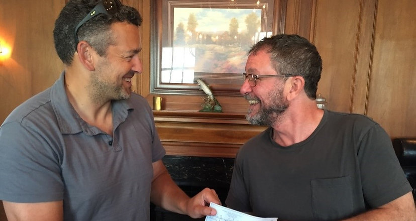 HVSF manager handing a check to a portfolio company CEO.