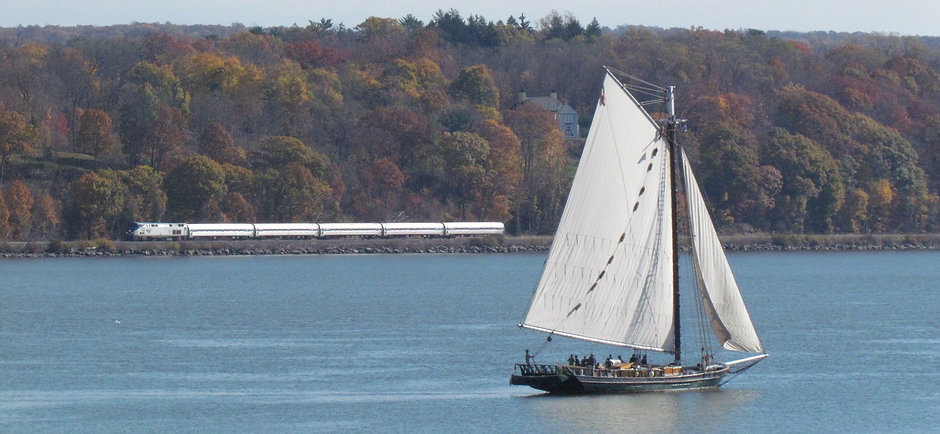 Clearwater Sloop on the Hudson River with Amtrak train in the background.