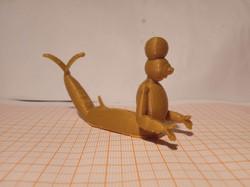 Toyart dourado impresso em 3D de um tritão de armadura, com uma bola na cabeça, com os braços pra fr