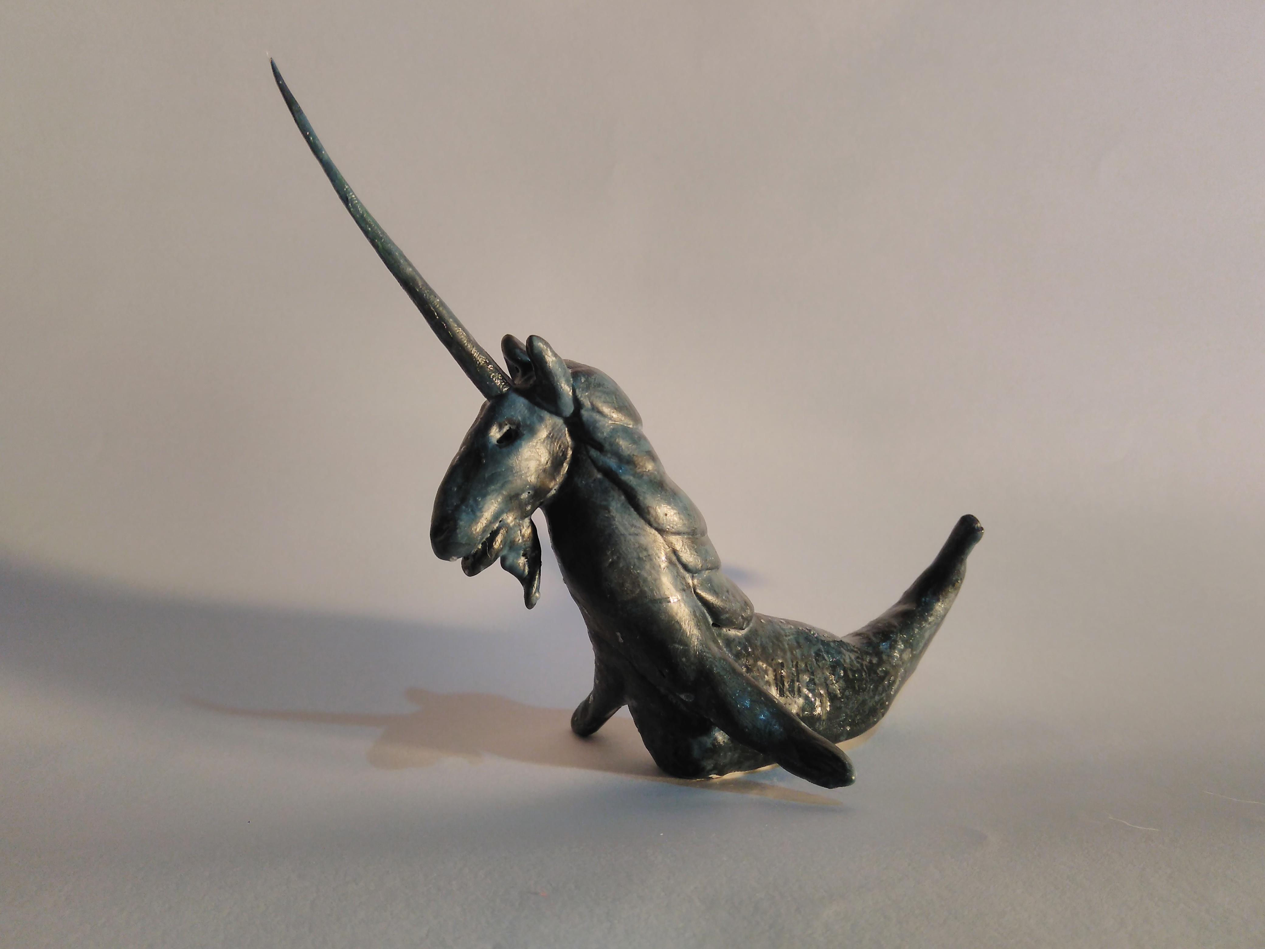 Personagem do Bosch feito em toyart: um cavalo preto com chifre e uma barbicha e com rabo de peixe v