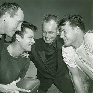 """Jesse Hibbs (AU 1929), 3rd from left, was a two-time Trojan football All-American tackle who then directed """"All American"""" starring Tony Curtis with ball and Frank Gifford, far right"""