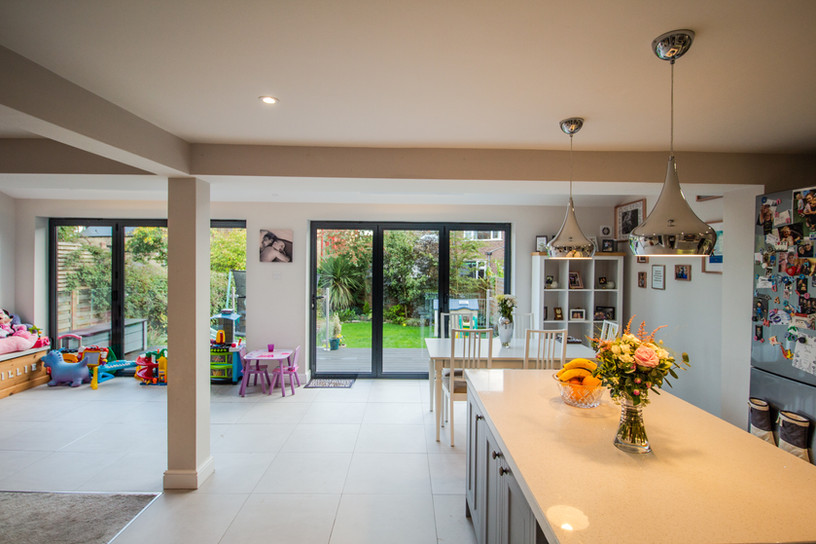 View of completed open living, kitchen and dining space. Swipe right to see image before extension.