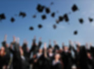 University students tossing their caps at graduation