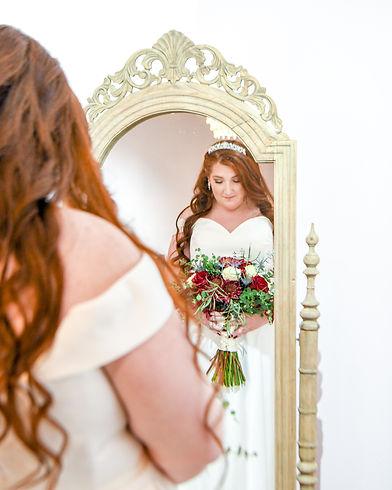 Bride with wedding bouquet looking in mi
