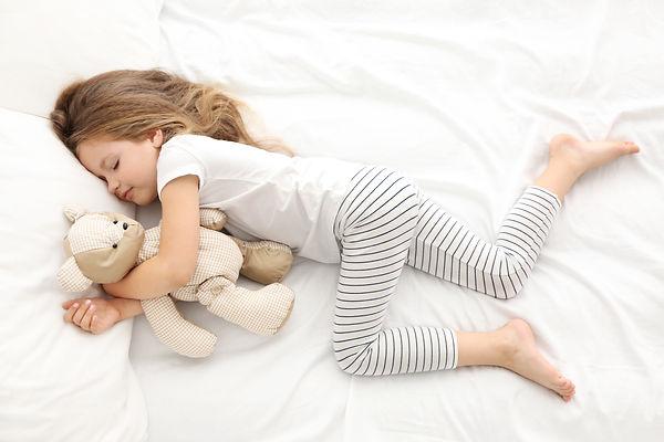 Cute little girl sleeping with teddy bear in bed.jpg