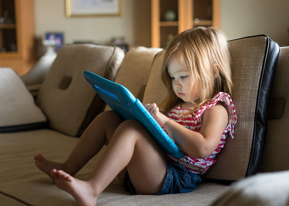 Young girl sitting at home on settee and using a child's tablet touch screen computer.jpg