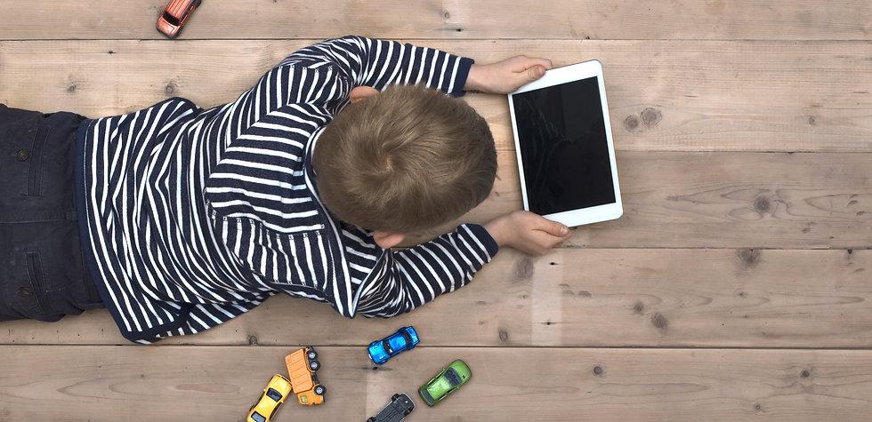 Modern generation. Kid playing on ipad.j