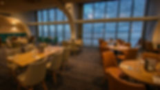 A photograph of the inside of a restaurant at night looking out over the beach
