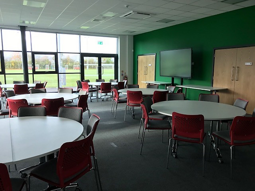 A photograph of a  meeting room inside Colliers Park with tables and chairs in it