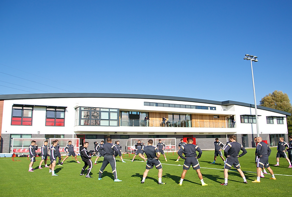 Photograph of Dragon Park football training centre building with a group of people standing on a football pitch outside it stretching