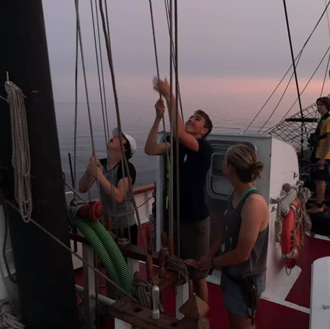 Trainees setting the square sails as night watch begins.