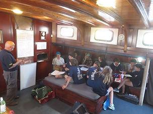 Trainees receiving a lesson below deck. Summer camp.