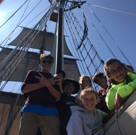 Trainees working together to set Black Jack's sails.