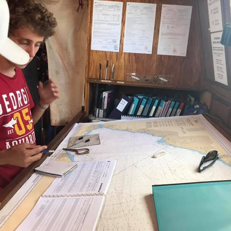 Trainee learning how to complete a ship's log and plot Fair Jeanne's location on a chart.