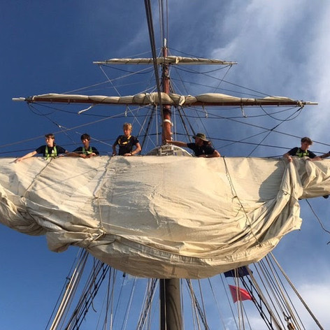 Crew and trainees working together to furl the course on Fair Jeanne.