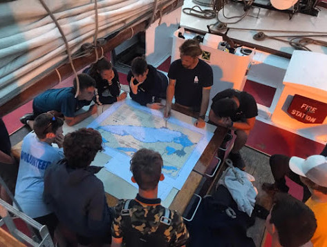 Captain explaining to the trainees where they've sailed the past 10 days.