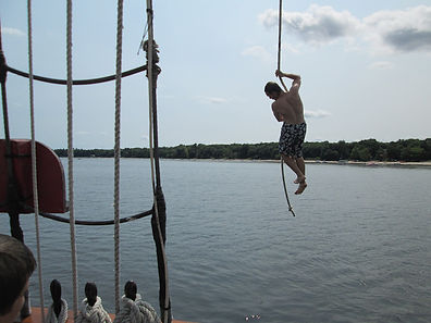 Rope swing into the water. Summer camp.
