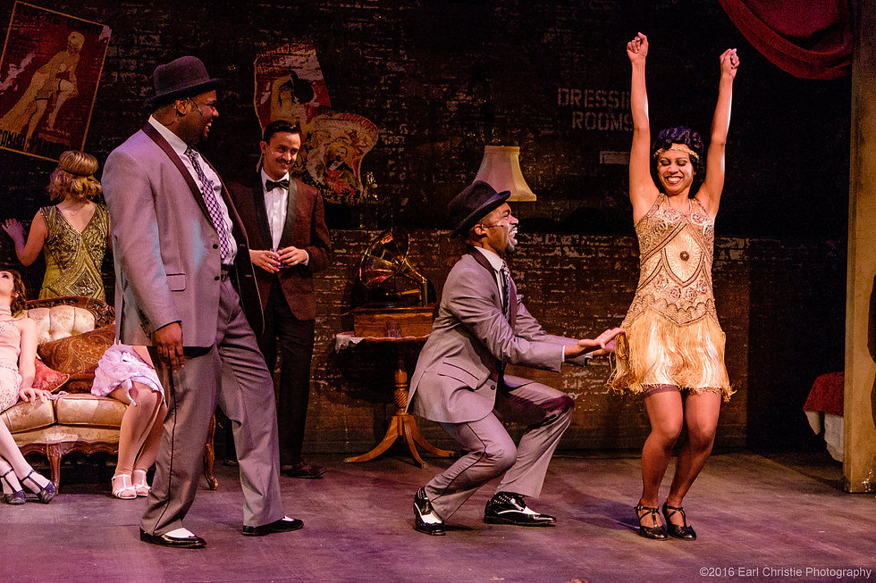 Carla with her arms raised in a gold, Gatsby dress. She is surrounded by three men in suits.
