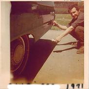 Man crouching beside car