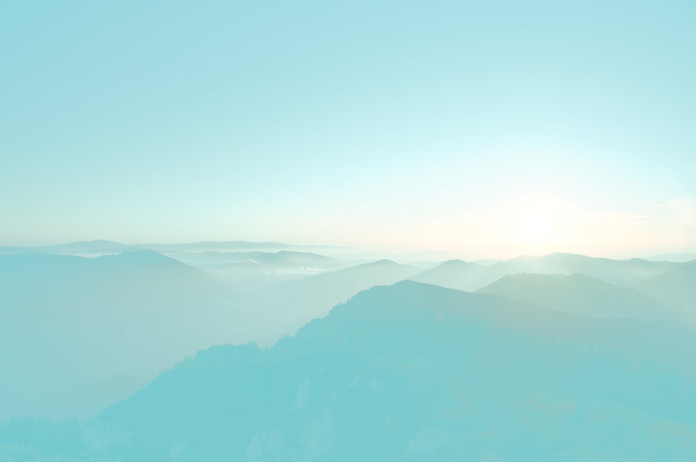 Soft focus hazy photo of overlapping mountain ranges and sky with overall bluish tint.