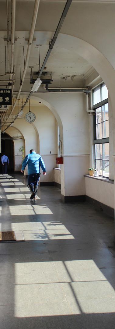 長靴のオッサン連が行きかう廊下。ゆるやかなカーブ、大きくとられた窓、柱のゆるいアーチの意匠もいい。ここは、おえらいさんも行きかう廊下。機能だけじゃなく、デザインにもこだわったんですなあ。