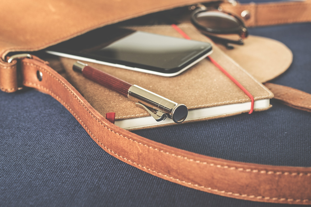 journal, pen, mobile, and sunglasses spilling out of a bag