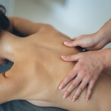 topless-woman-lying-on-bed-getting-massa