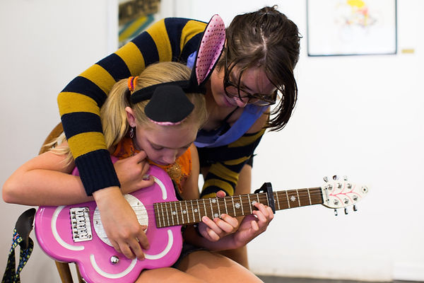 Rock Camp Counelor Helping Youth Play Guitar