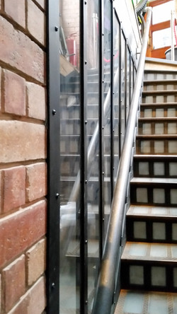Steel and glass window and steel handrail for stairs built by Stairworks