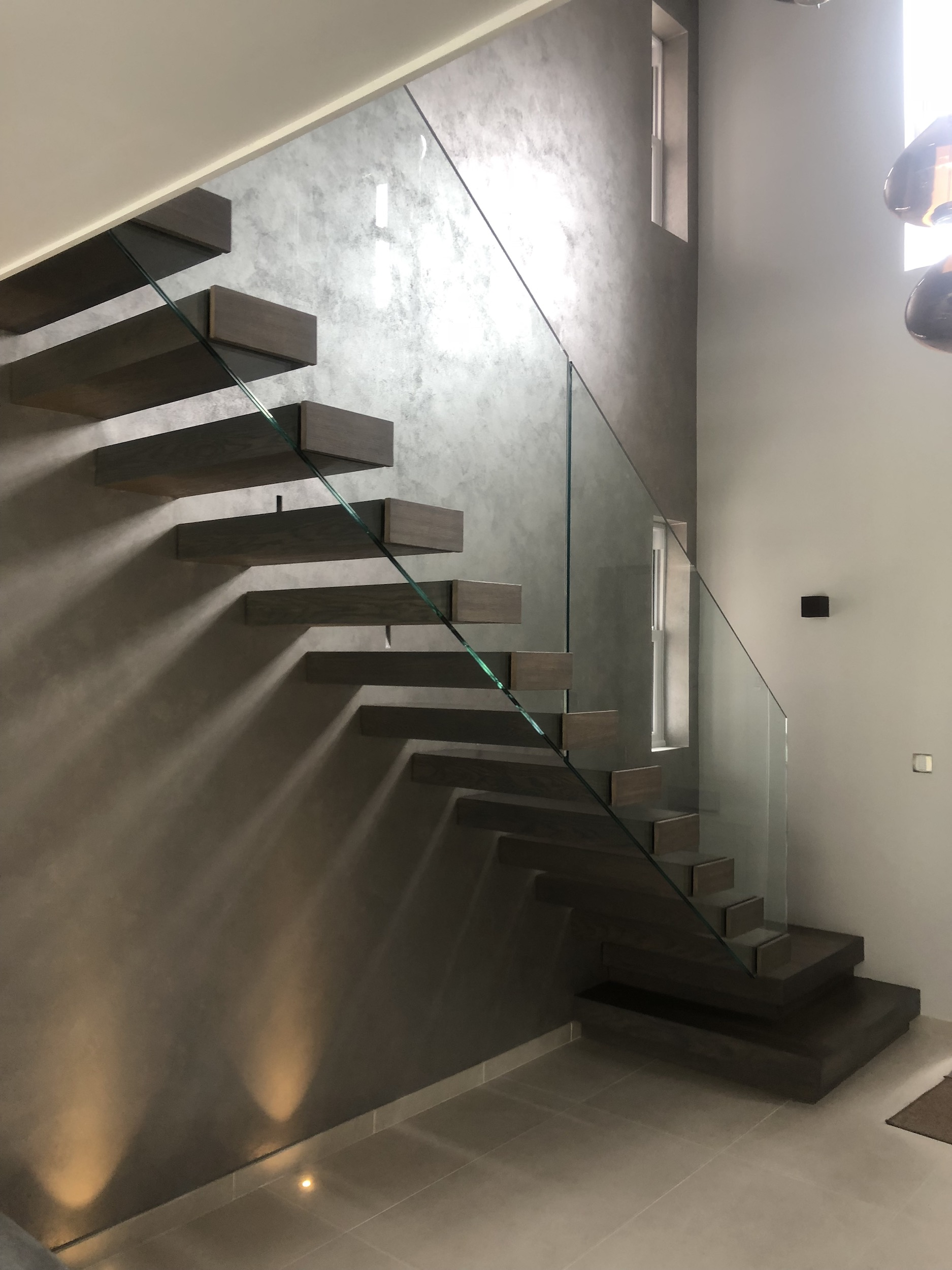 Floating staircase in Auckland with timber treads and glass balustrade