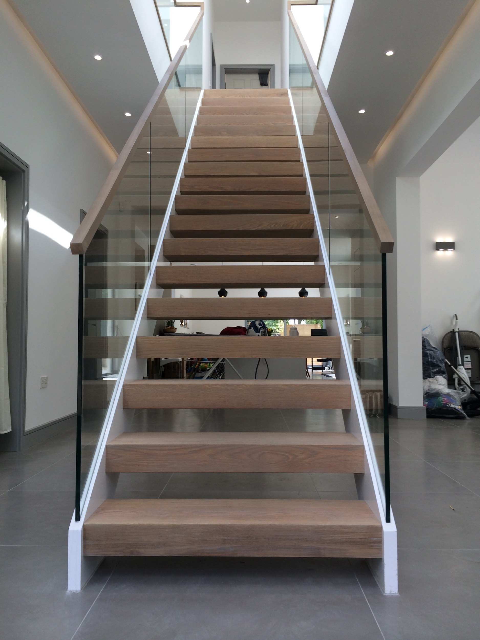Symmetrical staircase with timber treads and glass balustrades