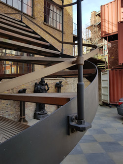 Steel spiral staircase with wood treads by Stairworks