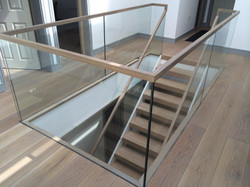 Wooden handrail slotted over glass in perfect symmetry