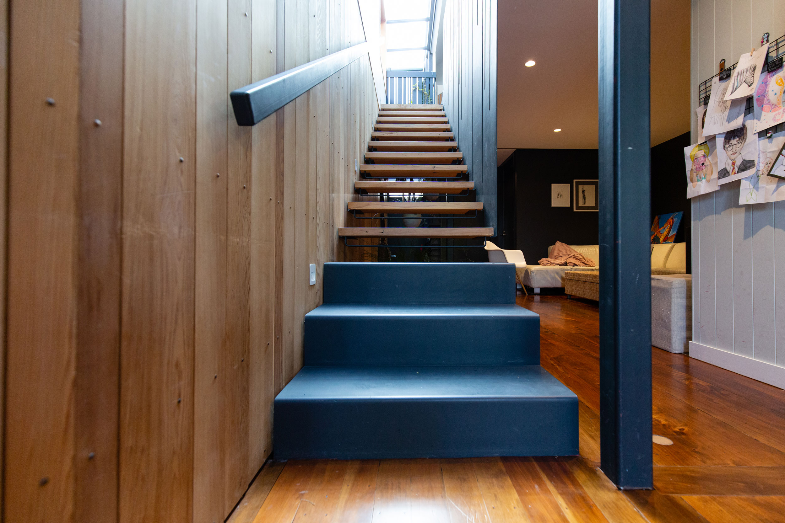 Floating staircase with timber treads and steel balustrade built by staircase design company Stairwo
