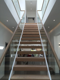 Symmetrical stairs with open risers, timber treads and glass balustrade