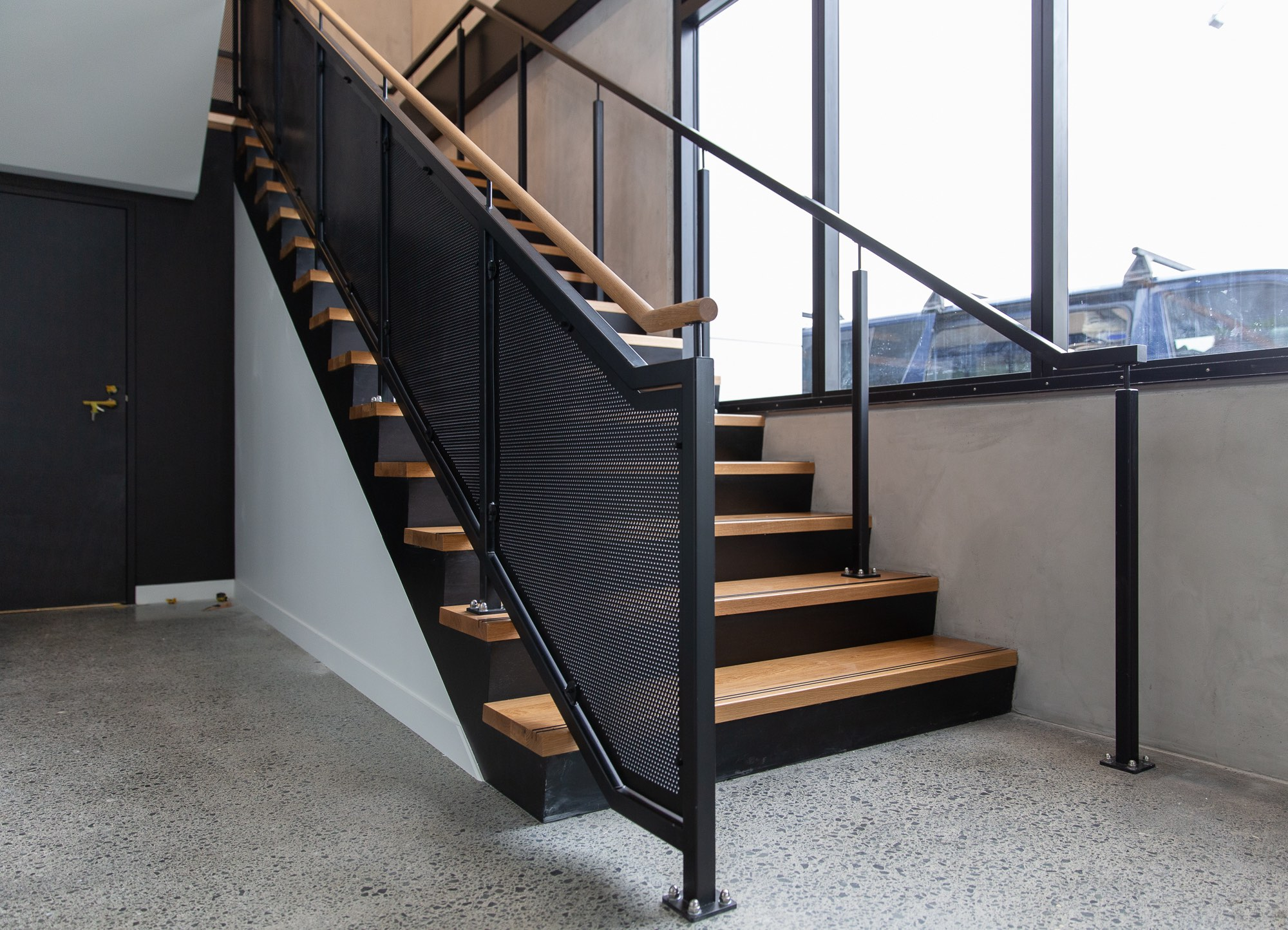 Commercial staircase design by Stairworks in Auckland with metal balustrade, oak treads and handrail