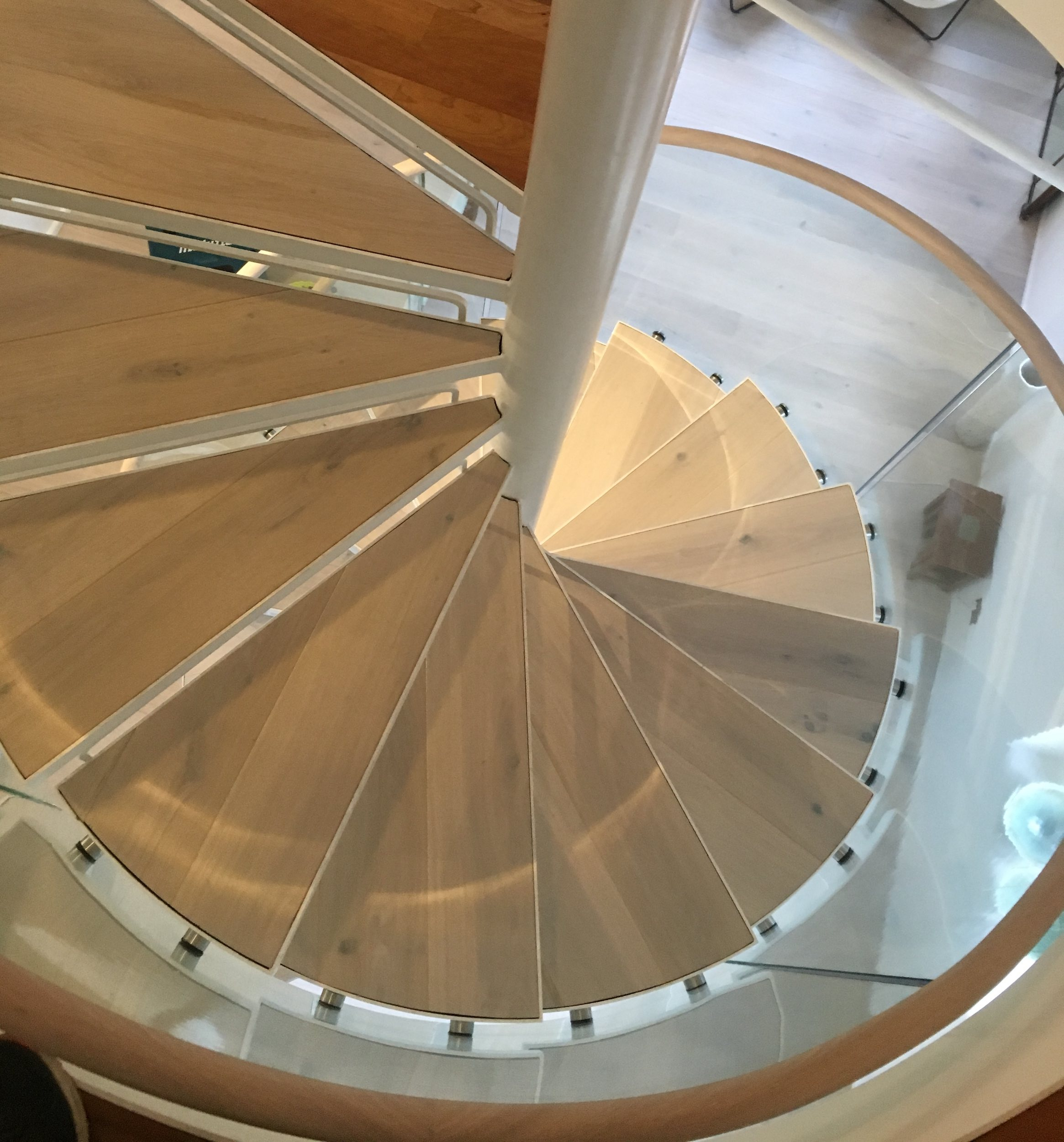 Spiral staircase with reclaimed wood treads and glass balustrade
