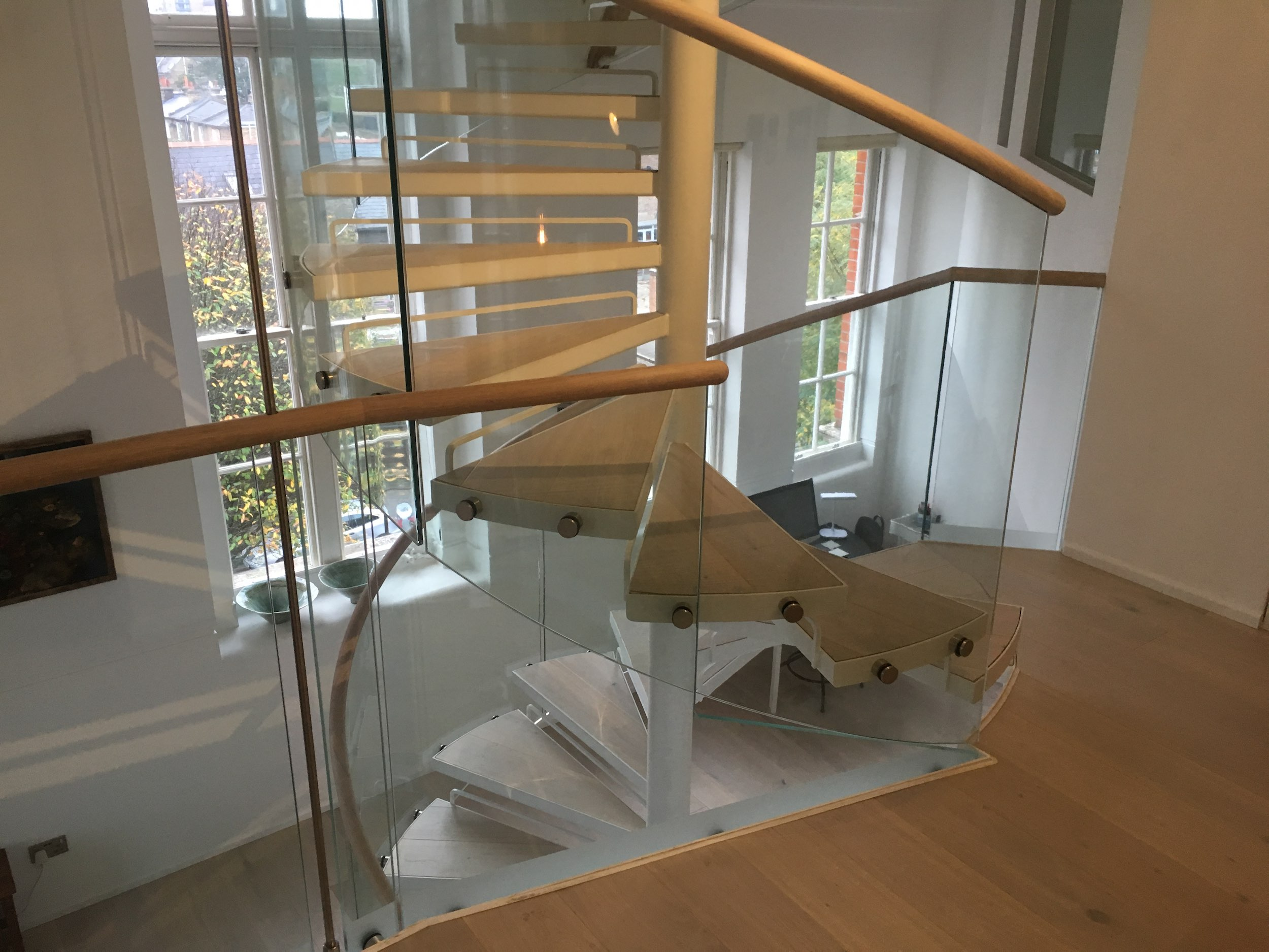 This spiral staircase is made of steel, reclaimed wood, and glass