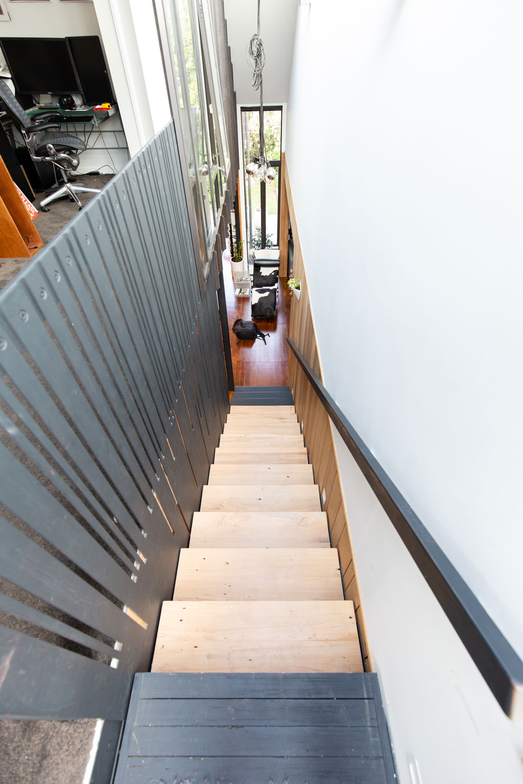 Slotted metal balustrade was designed by Stairworks to allow light through to the downstairs