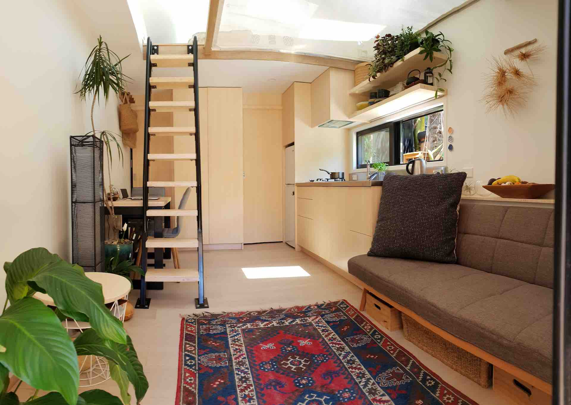 Metal ladder in New Zealand tiny home with wood treads