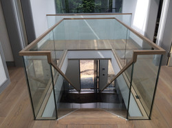Glass balustrade and wooden railing on straight staircase