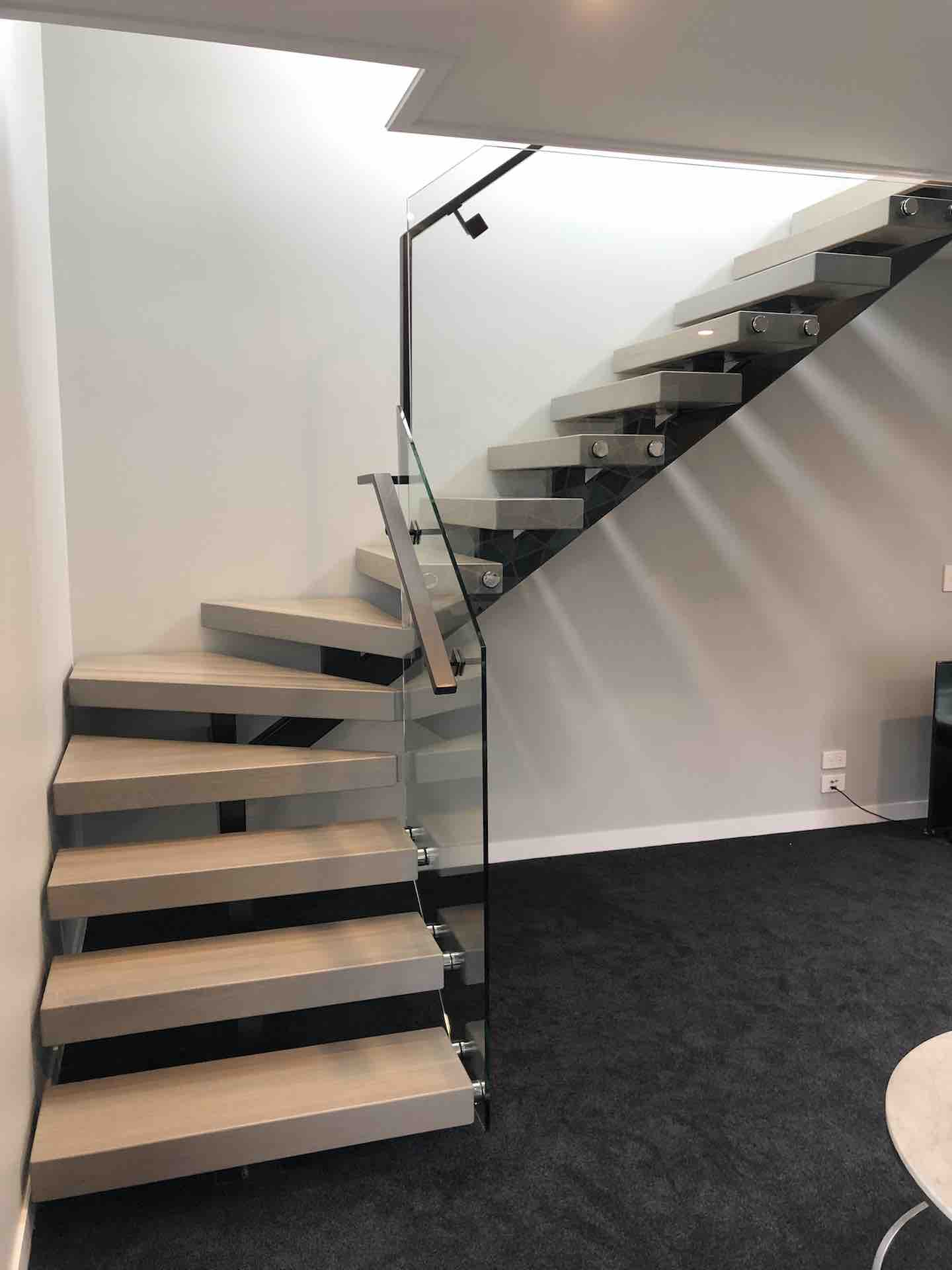 Floating stairs allow light in to show home in Auckland