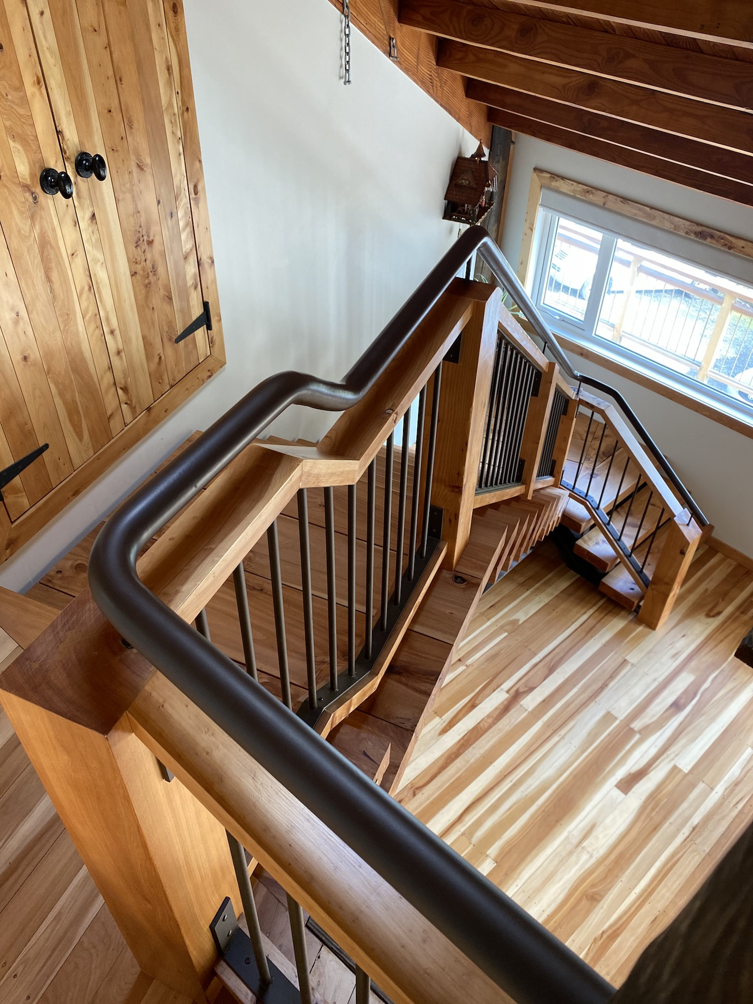Rustic staircase with reclaimed wood treads and steel handrail
