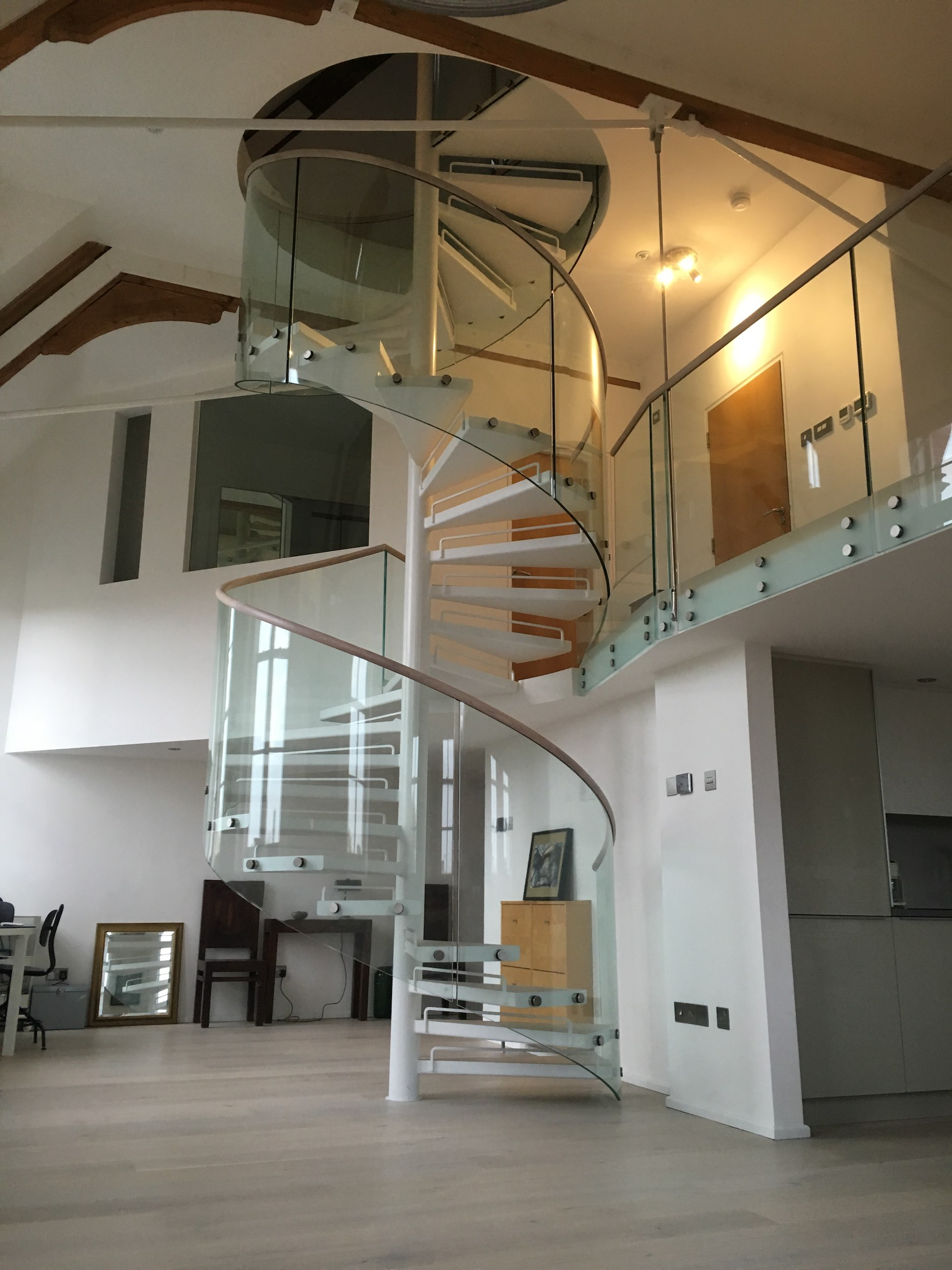 These NZ spiral stairs achieve the minimal look with open risers and glass balustrades