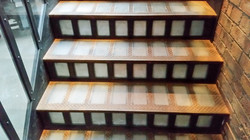 Metal staircase with glass risers designed and built by Stairworks