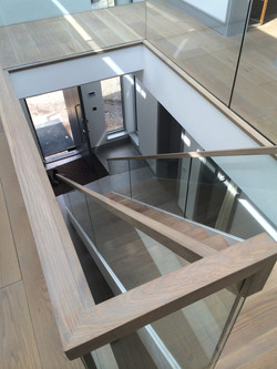 Wooden railing on straight staircase with glass balustrade